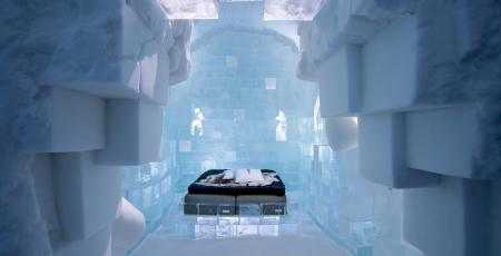 overview of art suite made of ice and snow with double bed with reindeer hides