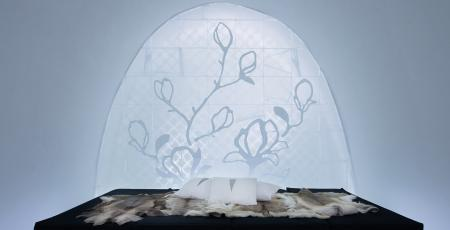 a bed covered with reindeer hides surrounded by beautiful ice art at icehotel