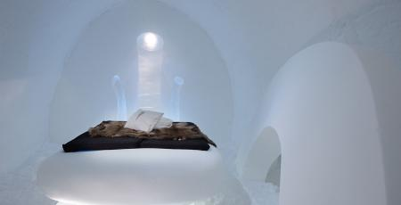 A bed of snow in the shape of the core of an apple in a room of snow at icehotel