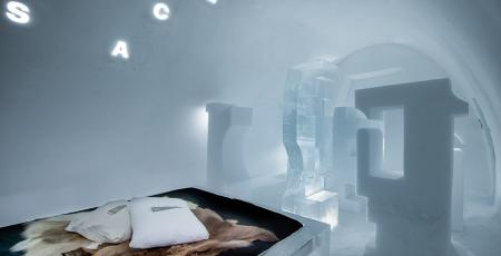 double bed with reindeer hides in a room of ice in Icehotel