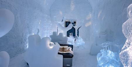 bedroom filled with figurative ice art inside Icehotel