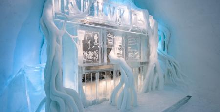 hot dog stand in ice covered by roots of snow inside Icehotelbed with reindeer hides in room with walls of snow in Icehotel