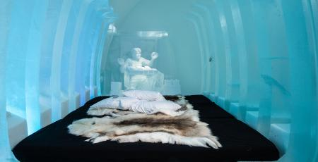 a bed covered with reindeer hides surrounded by ice in icehotel
